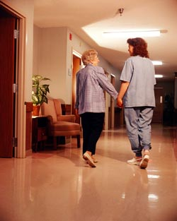 A caregiver walking a woman down a hallway.